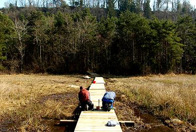 Civiliste construisant une passerelle en bois
